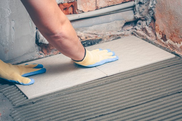The tiler barks and fixes his hands in yellow gloves a square tile on the floor