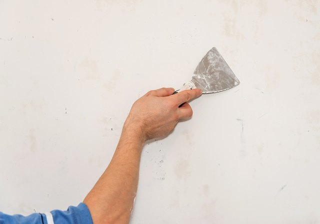 Painting worker repair wall using a paint spatula hand