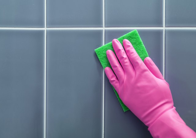 Hand washes the tile.