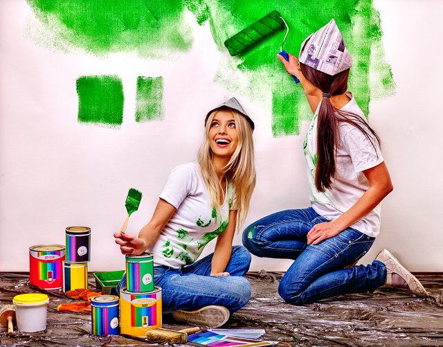 Woman paint wall at home