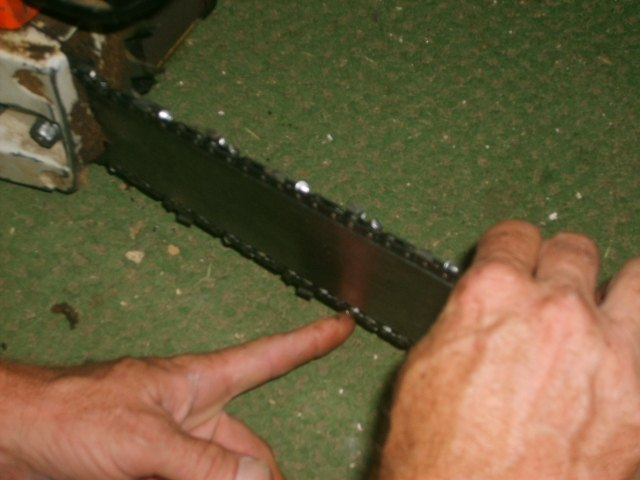 How to put a chain back on a chainsaw hunker check the tightness of the chain greentooth Choice Image