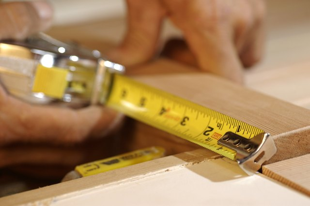 Close-up of man's hands as he measures a piece of wood.