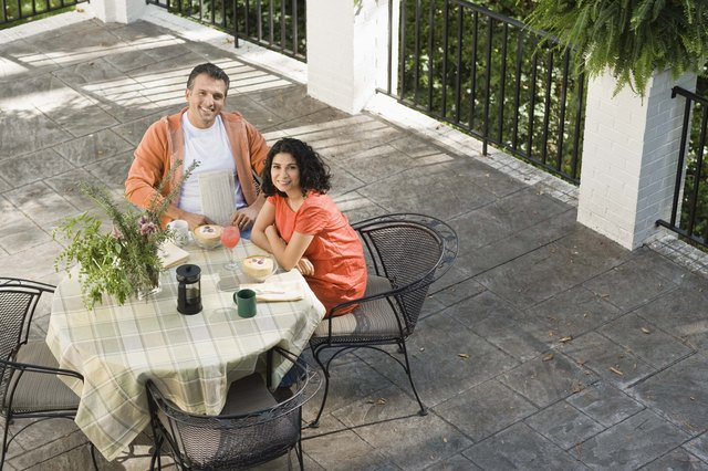 Couple having drinks at table on veranda
