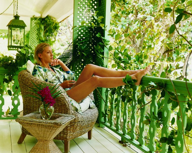 Young Woman Sitting on Her Balcony in a Wicker Chair With Her Feet Up on a Railing Holding a Glass of Water