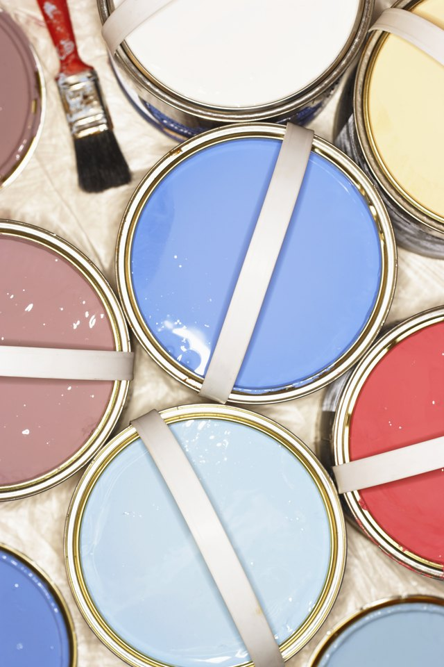 Open tins of paint on plastic covered floor, overhead view