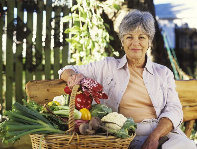 Senior woman with basket of vegetables, smiling, portrait