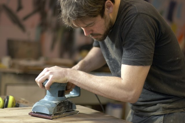 Carpenter Using An Electric Planer In Workshop