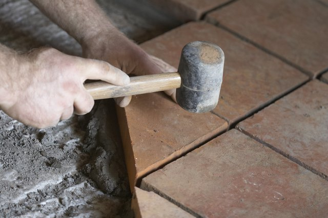 Builder Laying Quarry Tiles