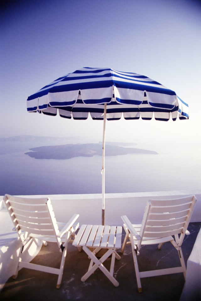 Rear view of wooden chairs and a table with umbrella on a balcony overlooking the ocean and the Greek Isles.