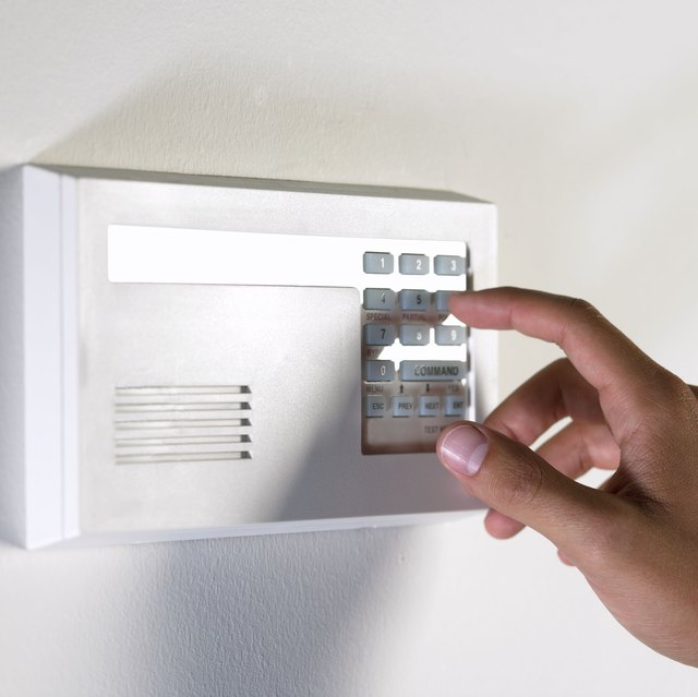 Hand pushing buttons on alarm system