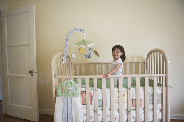 Toddler girl standing in her bedroom crib
