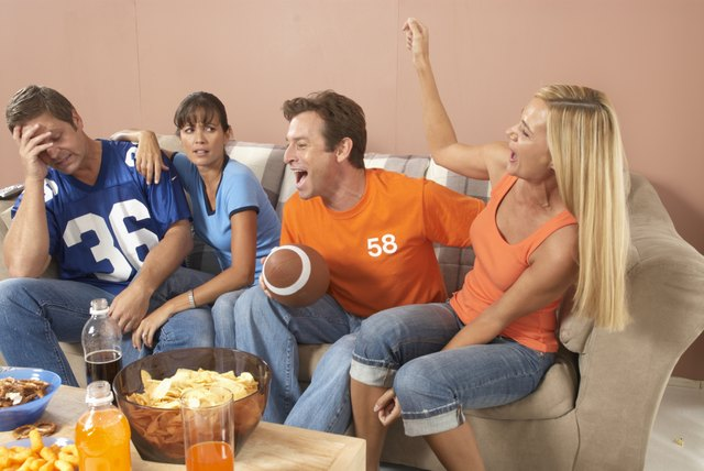 Two couples watching football in living room