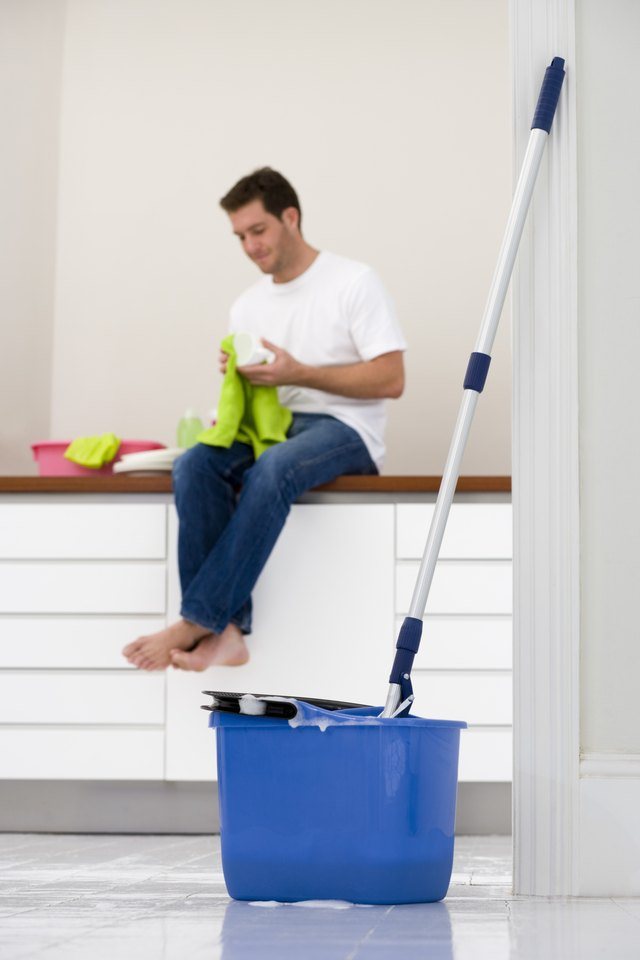 Man Sitting On Kitchen Counter With Mop And Bucket