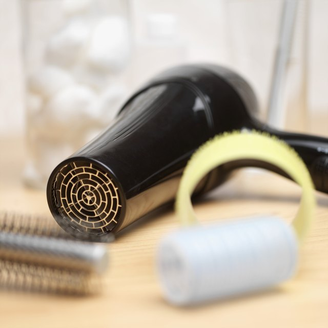 Close-up of a hair dryer, hairbrush and curlers