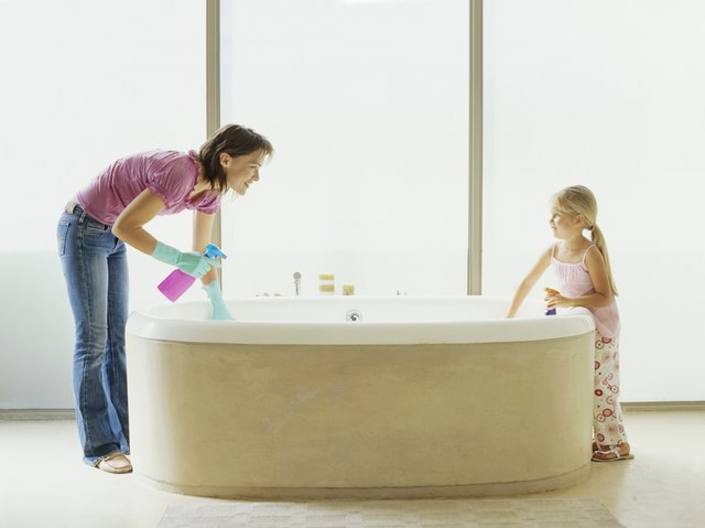 Side profile of mother and her daughter washing the bathtub