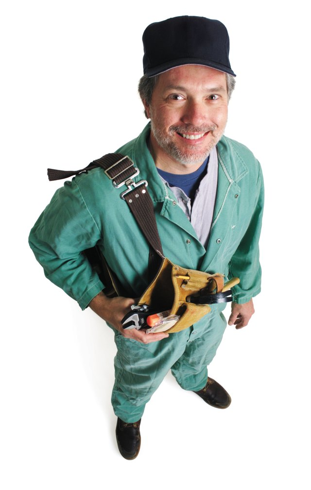 a caucasian male plummer in a green jumpsuit and a ballcap holds his tools and looks up at the camera