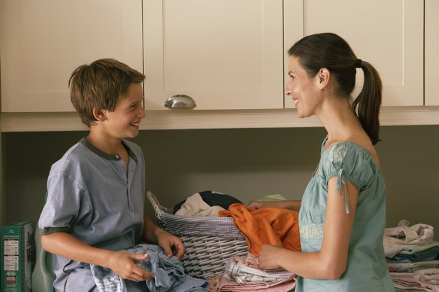 Son (9-11) helping mother with laundry, smiling