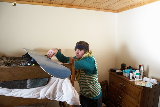 Young man leaning on bunk bed with snowboard, portrait