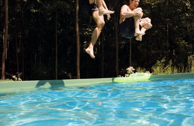 People jumping into a swimming pool.