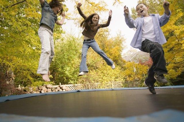 Siblings jumping on trampoline