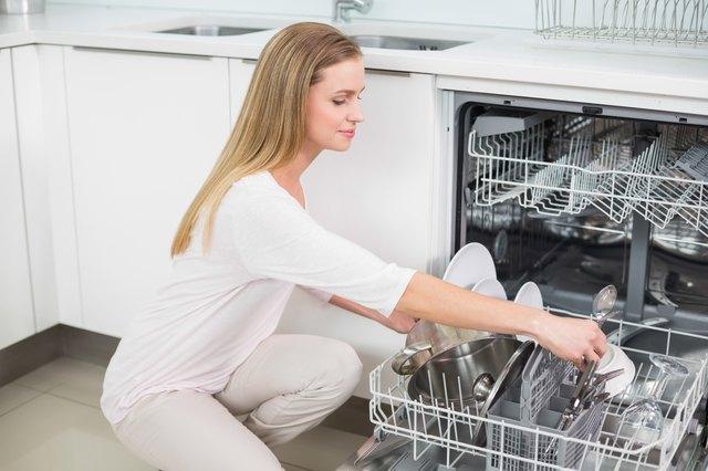 Calm gorgeous model kneeling next to dish washer