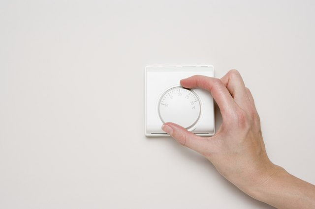 Person turning thermostat