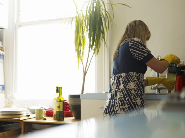 Young woman washing up at kitchen sink, rear view