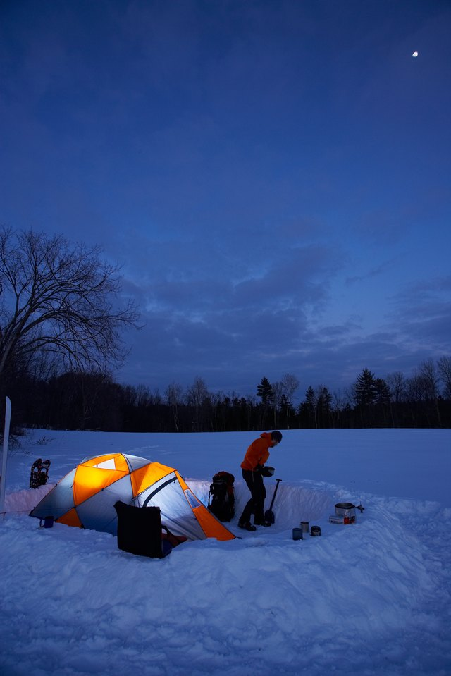 Illuminated tent and person at night in winter