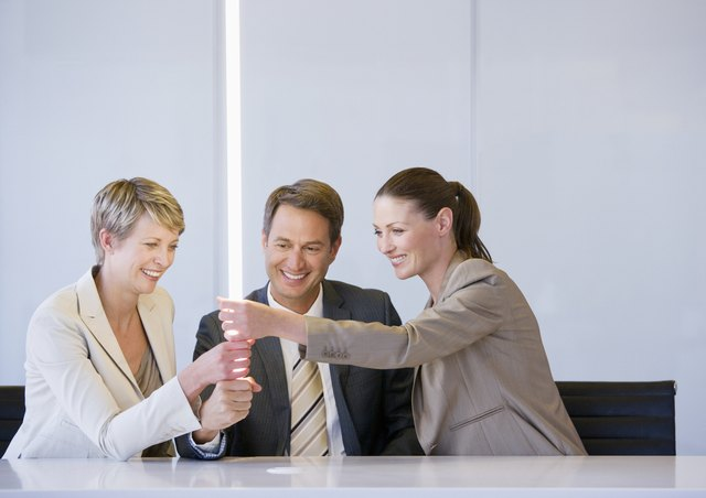 Business people holding glowing light in conference room