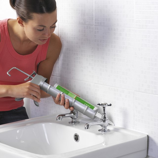 Woman applying sealant between a wall and a sink