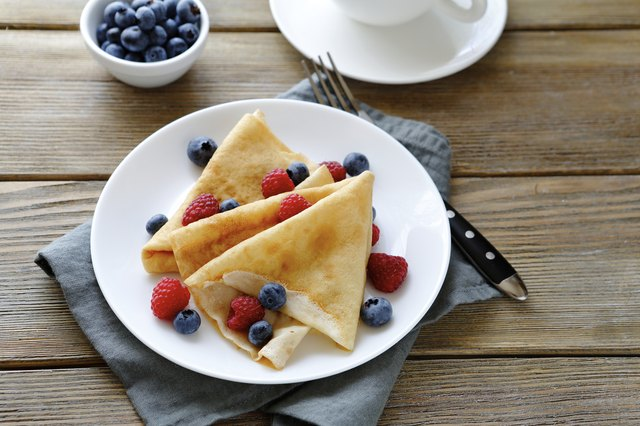 summer crepes with berries on white plates
