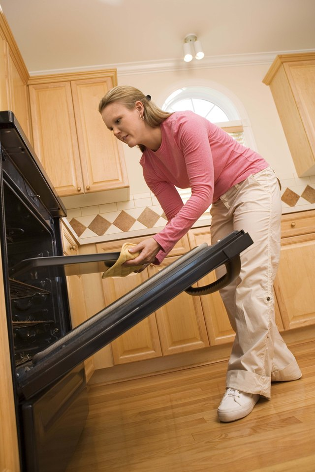 Woman removing tray from oven