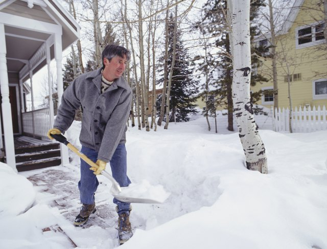 Man shovelling snow from walkway outside house