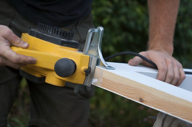 Carpenter using an electric planing tool on a door frame