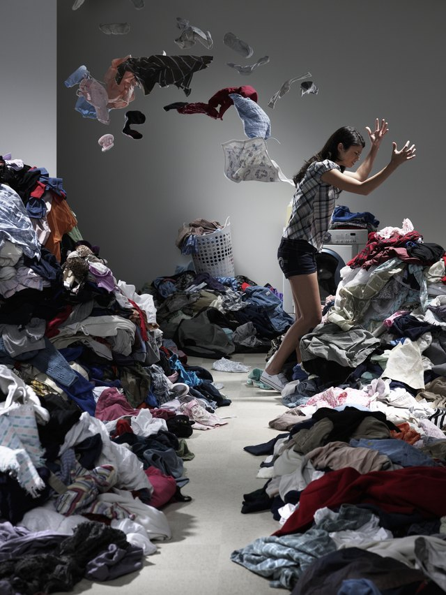 Woman throwing clothes in overflowing laundry room