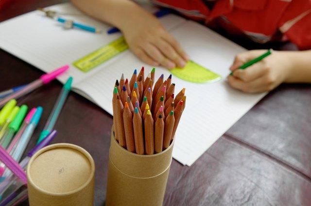 Boy (6-8) using protractor, focus on pot of pencils, close up