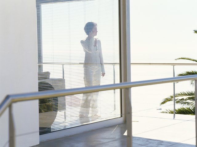 mid adult woman standing behind blinds and talking on a mobile phone