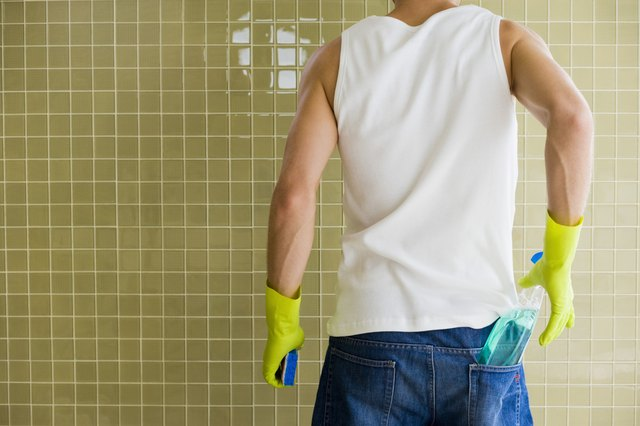 Man cleaning shower wall