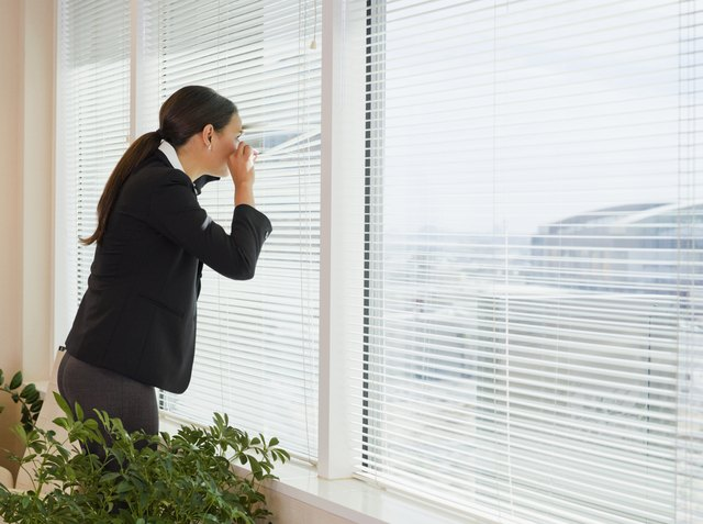 Mixed race businesswoman peering out window