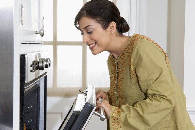 Woman looking in oven in kitchen