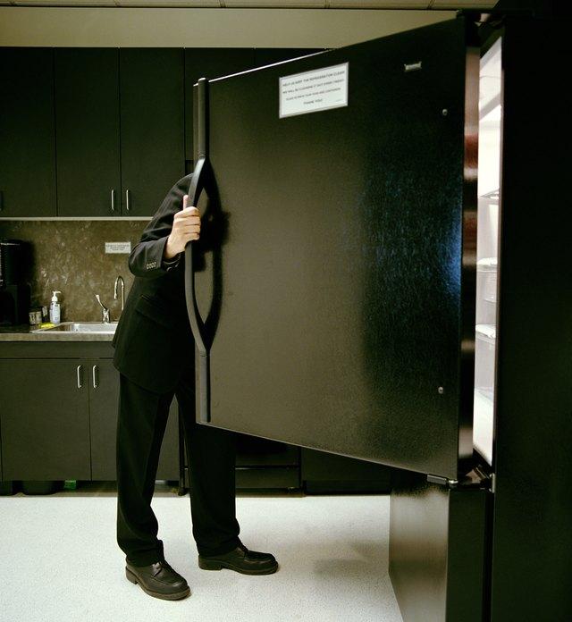Mature businessman looking in refrigerator in office kitchen