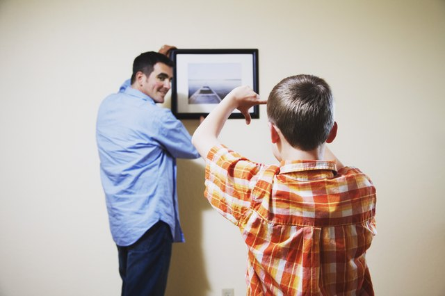Son helping father straighten picture