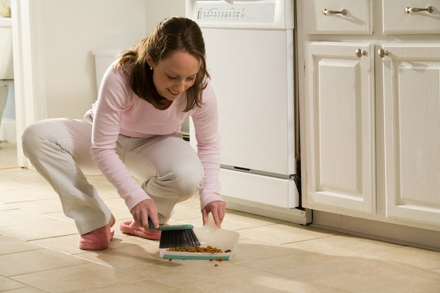 Woman cleaning spilled dog food off kitchen floor