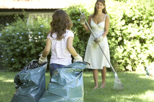 Mother and daughter (6-7) in garden, daughter holding garbage bag, mother raking grass
