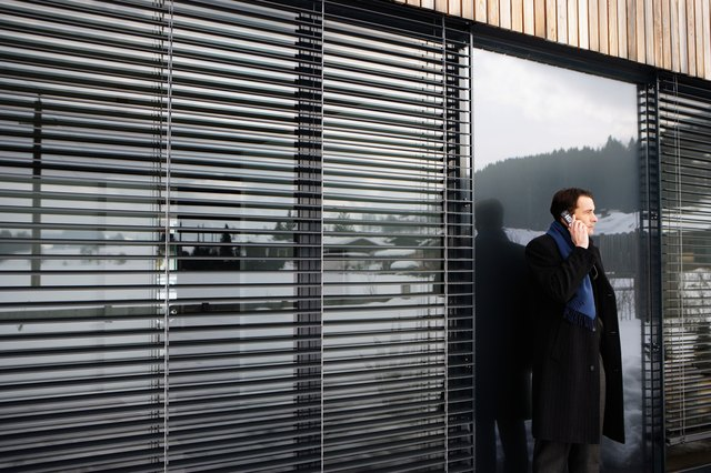 Man using mobile phone, snow-covered land reflected in windows