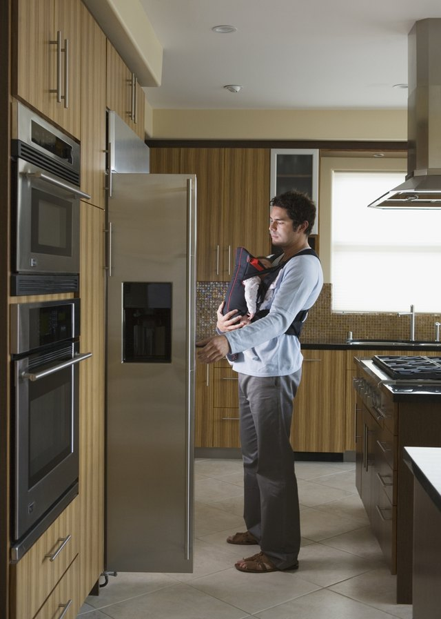Hispanic father and baby looking in refrigerator