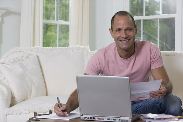 Hispanic man sorting out bills in front of a laptop