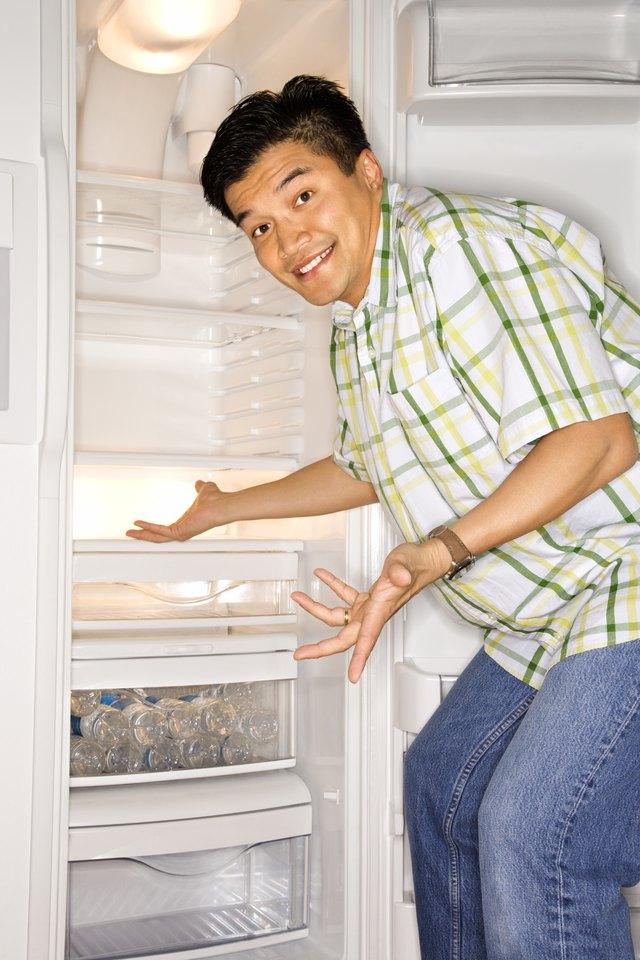 Man gesturing in front of refrigerator