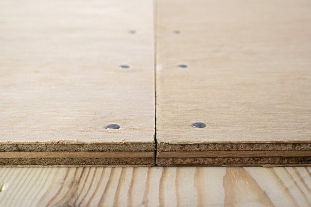 Butt joint on plywood nailed to wooden floor, close-up