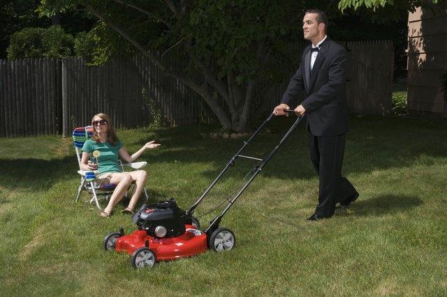 Mature woman sitting in deckchair, butler mowing grass